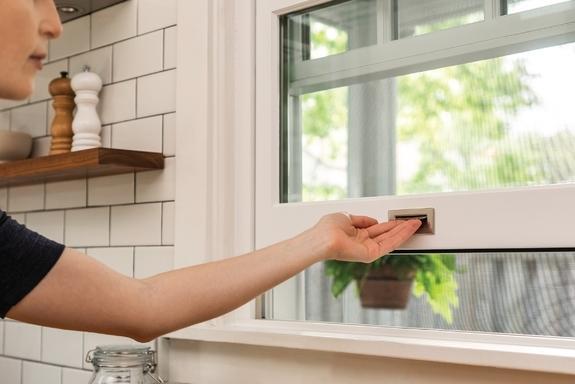 woman opening kitchen window marvin windows