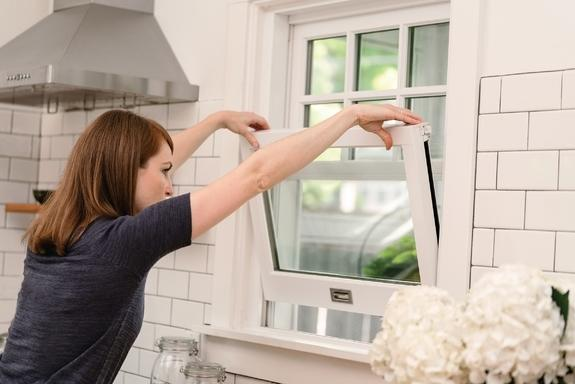 woman opening window in kitchen for washing marvin windows