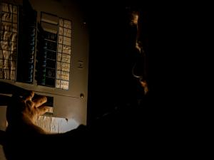 person checking breaker box of home in the dark during a power outage at home