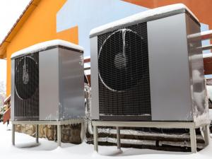 heat pump outside of home covered with snow