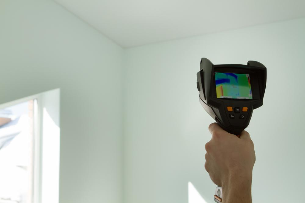 technician using thermal imaging inside home